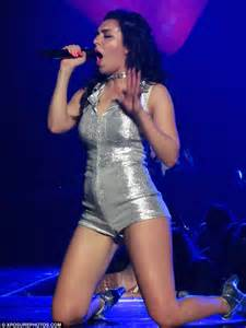 Charli XCX onstage in a silver hot pants onesie
